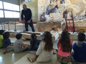 Teacher/Guide and Tinos Marble Crafts Museum and his captivated young audience